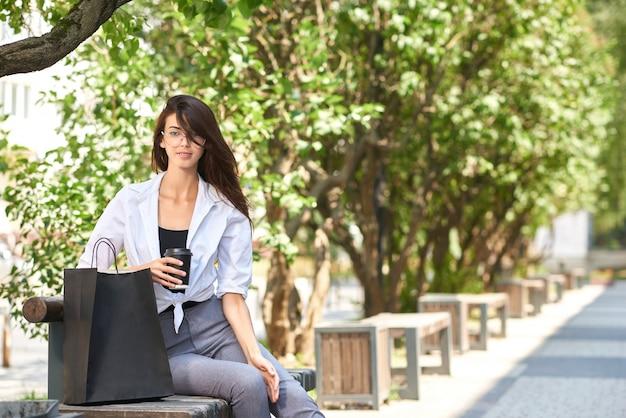 Jolie brune, buvant du café assis sur un banc en bois près de sacs en papier.