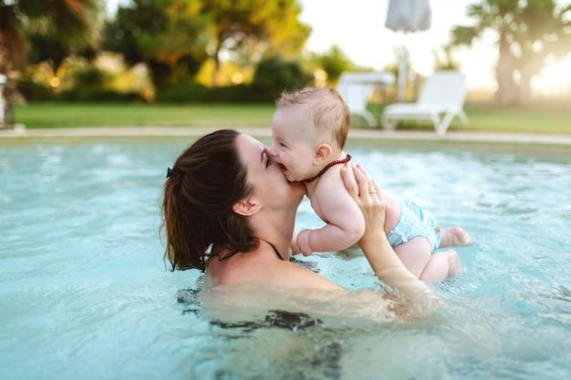 Jolie brune caucasienne dédiée embrassant son fils de 6 mois aimant en se tenant debout dans la piscine. première fois au concept de piscine.