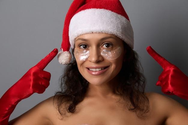 Une jolie brune en costume de père noël pointe du doigt les patchs oculaires sur son visage, sourit en regardant la caméra. publicité pour les salons de beauté pour les cadeaux de noël et du nouvel an. spa, concept de soins de la peau