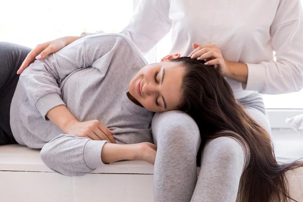 Jolie brune couchée sur les genoux de sa copine