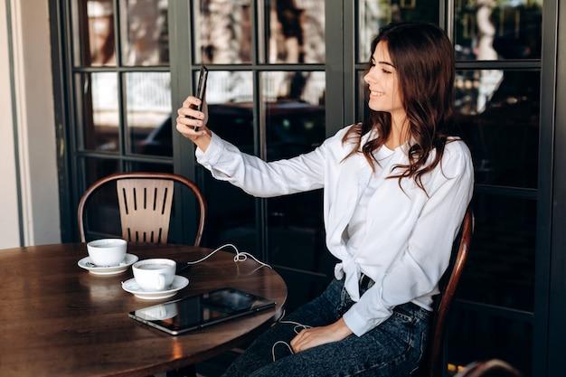 Jolie brune dans un café fait des selfies