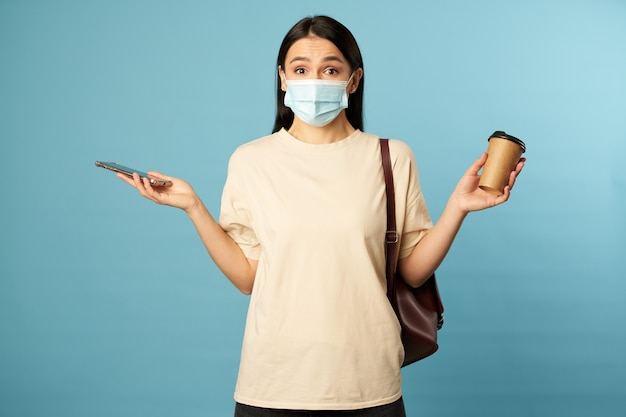Jolie brune dans un masque jetable et avec un sac à dos
