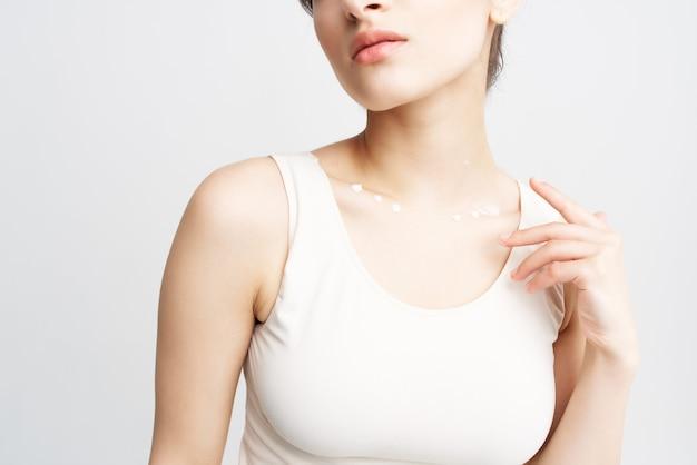 Jolie brune en débardeur blanc crème de santé pour la peau propre
