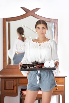 Une jolie brune est debout avec un plateau dans les mains avec un café et des biscuits, des serviettes, des décorations et une théière chinoise. bon petit déjeuner. routine matinale