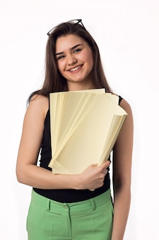Jolie brune étudiante jeune femme en pantalon vert avec des papiers