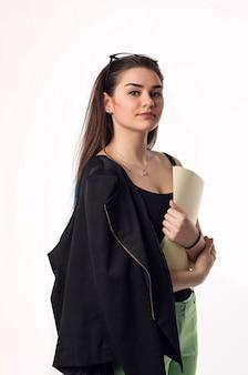 Jolie brune étudiante jeune femme en pantalon vert et veste noire avec des papiers