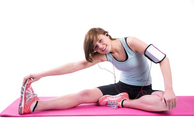 Jolie brune faisant la tendon d'ischio-jambiers sur le tapis d'exercice