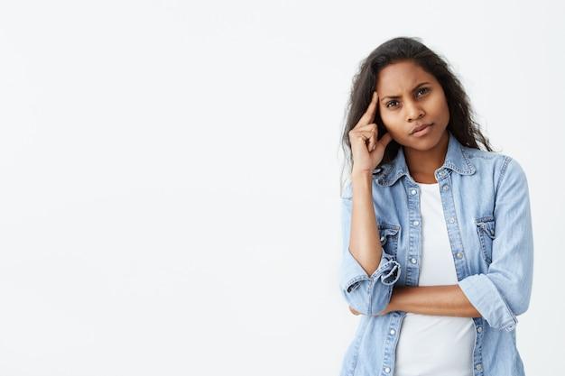 Jolie brune femme afro-américaine aux longs cheveux ondulés fronçant les sourcils tout en ayant un look placide et réfléchi. femme à la peau sombre pensive avec une expression perplexe en pensant