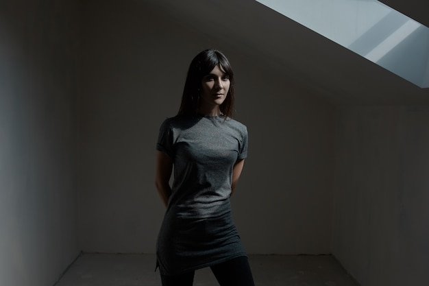 Jolie brune femme posant dans une pièce sombre