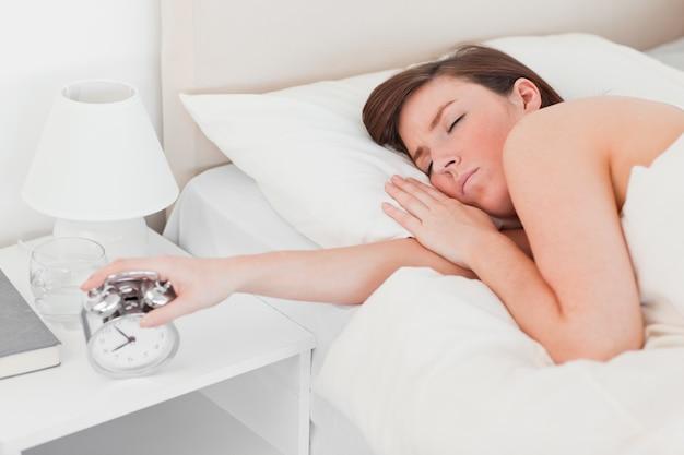 Jolie brune femme se réveiller avec une horloge en position couchée