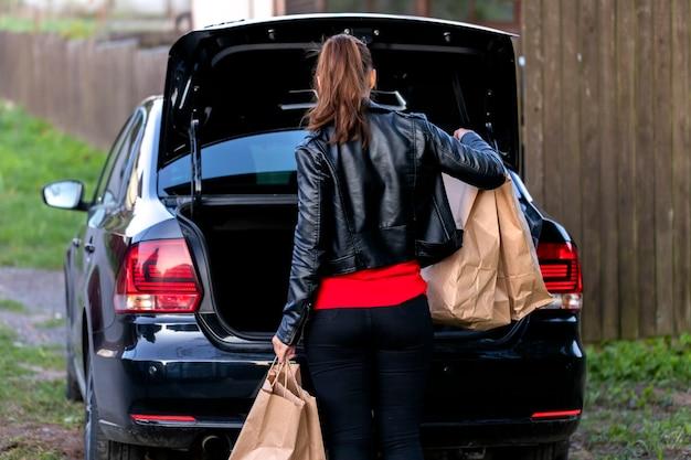 Jolie brune habillée avec désinvolture met des sacs en papier dans le coffre de la voiture noire