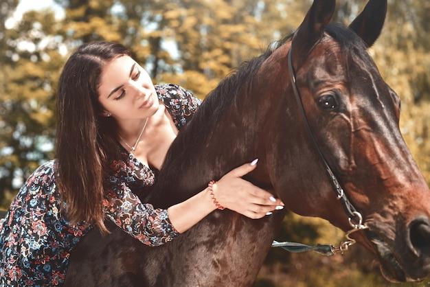 Jolie brune hispanique faisant un câlin à son cheval tout en le montant dans la forêt. aime les animaux concept. aimer les chevaux