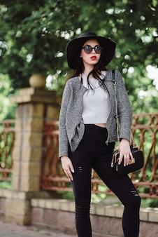 Jolie brune avec des lèvres rouges au chapeau et des lunettes de soleil posant dans la ville
