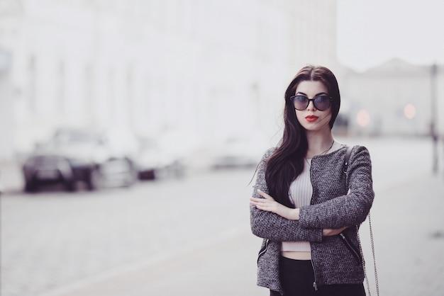 Jolie brune avec des lèvres rouges dans des lunettes de soleil posant dans la ville
