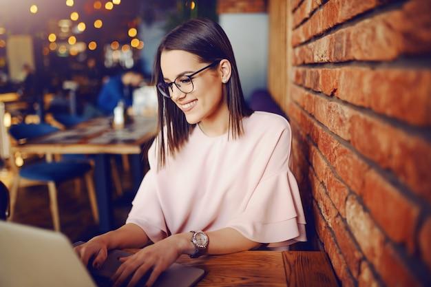Jolie brune avec des lunettes à l'aide d'un ordinateur portable assis dans une cafétéria