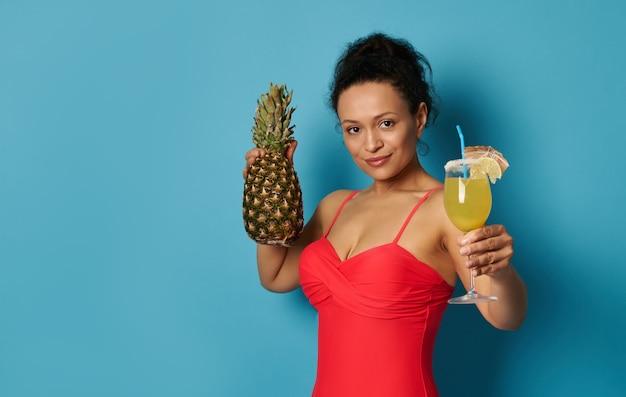 Jolie brune en maillot de bain avec un ananas à la main montrant un délicieux cocktail à la caméra, isolé