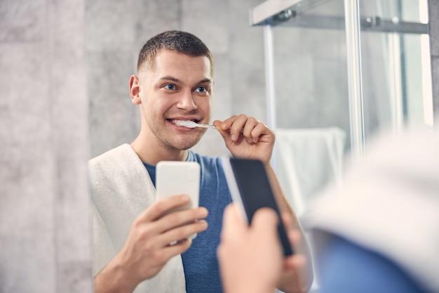 Jolie brune mâle nettoyant les dents du miroir tout en tenant le mobile à la main