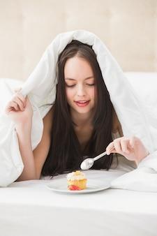 Jolie brune mangeant cupcake au lit