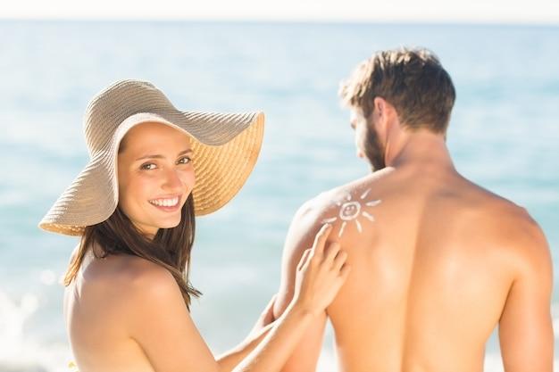Jolie brune mettant lotion de bronzage sur son petit ami