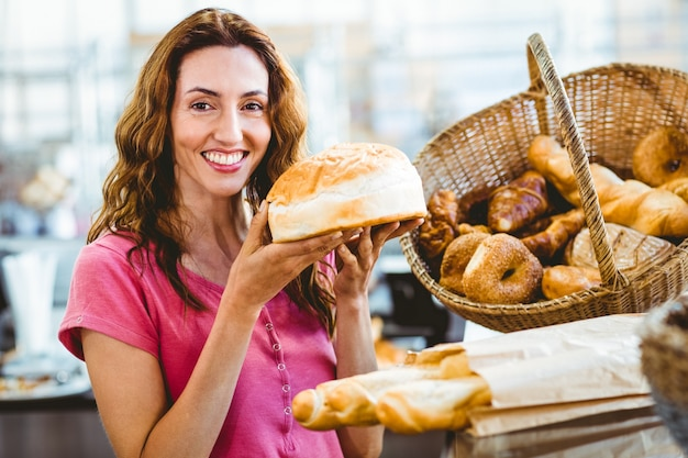 Jolie brune montrant une miche de pain