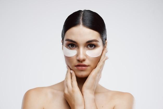 Jolie brune avec des patchs sur le rajeunissement des rides des soins de la peau du visage