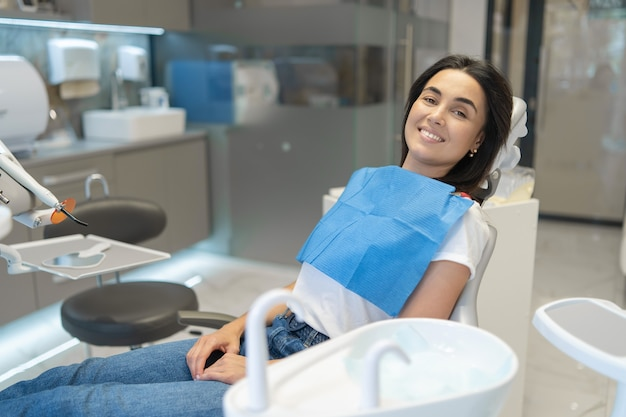 Jolie brune patiente heureuse assis dans la chaise à la clinique dentaire.