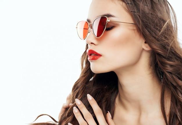 Jolie brune portant des lunettes de soleil glamour mode luxe posant