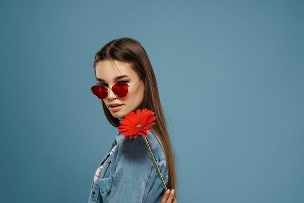 Jolie brune portant des lunettes de soleil modèle de style élégant fleur rouge