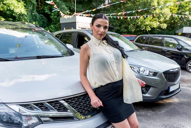 Jolie brune posant sur le capot d'une nouvelle voiture