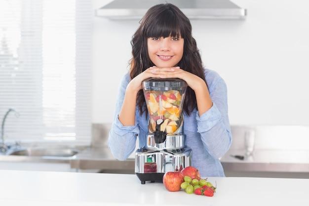 Jolie brune s'appuyant sur sa centrifugeuse pleine de fruits
