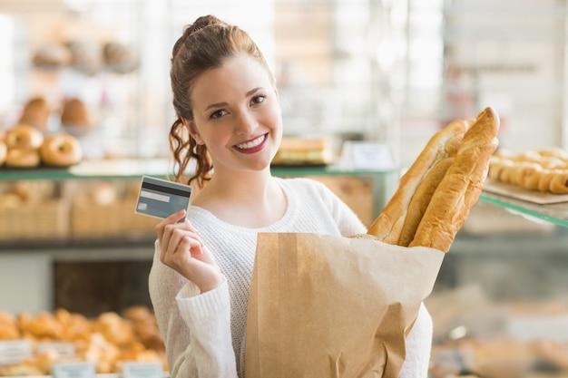 Jolie brune avec un sac de pain et une carte de crédit