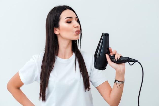 Jolie brune se dresse sur une surface de mur blanc avec un sèche-cheveux dans ses mains