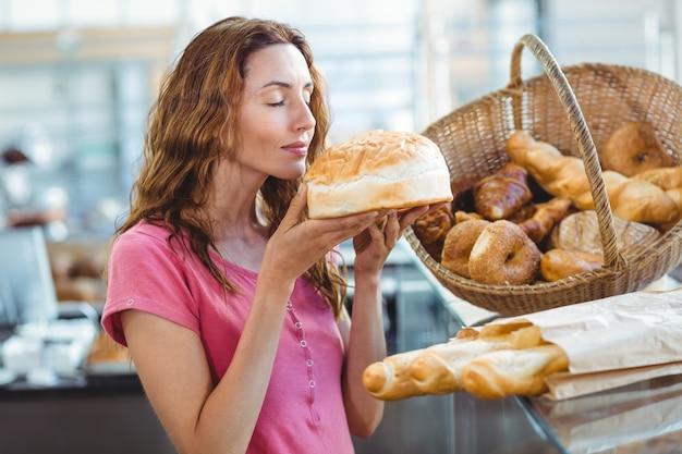 Jolie brune sentant la miche de pain