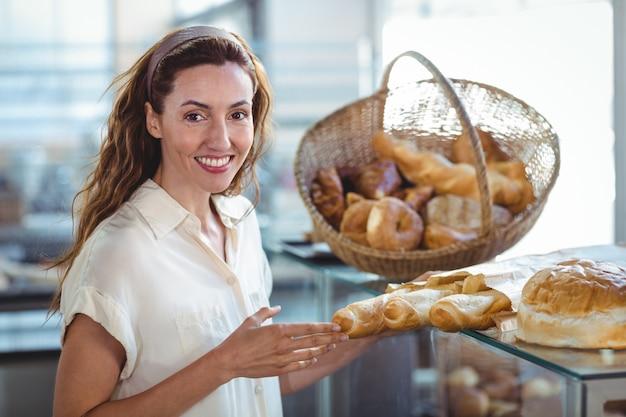 Jolie brune, souriant à la caméra et tenant une miche de pain