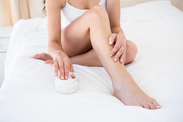 Jolie brune en utilisant la crème pour le corps sur le lit