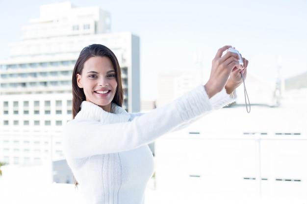 Jolie brunette prenant selfie avec caméra