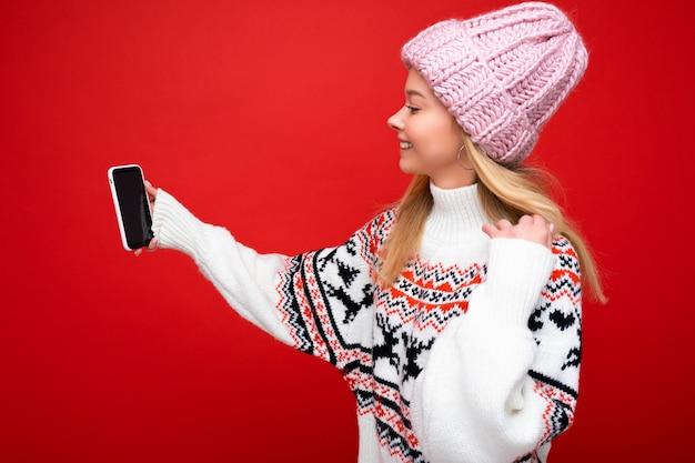 Jolie charmante jeune femme souriante et heureuse tenant et utilisant un téléphone portable prenant un selfie portant des vêtements élégants isolés sur fond de mur.