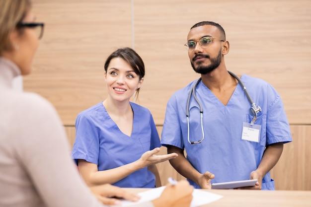 Jolie clinicienne en uniforme souriant au patient tout en présentant son professionnel ou collègue compétent dans les questions importantes