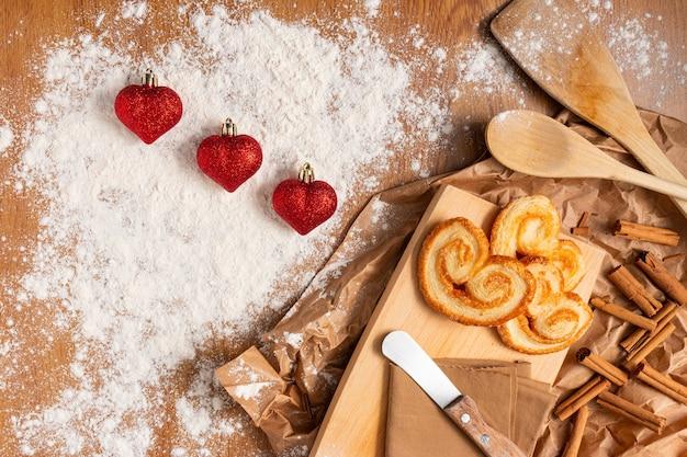Jolie composition pour la saint-valentin avec des pâtisseries et des bâtons de cannelle