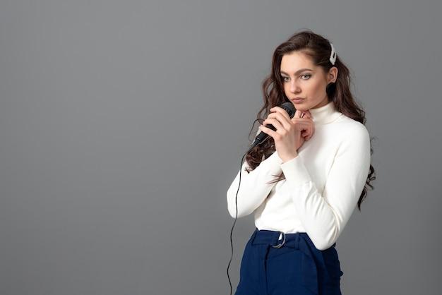 Une jolie conférencière pendant la présentation, tient un microphone et fait quelques gestes, isolée sur fond gris
