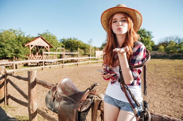 Jolie cowgirl rousse au chapeau de paille envoyant un baiser d'air alors qu'il était assis sur la clôture
