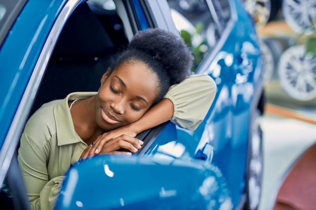 Jolie dame africaine aimait l'automobile dans la salle d'exposition de voitures