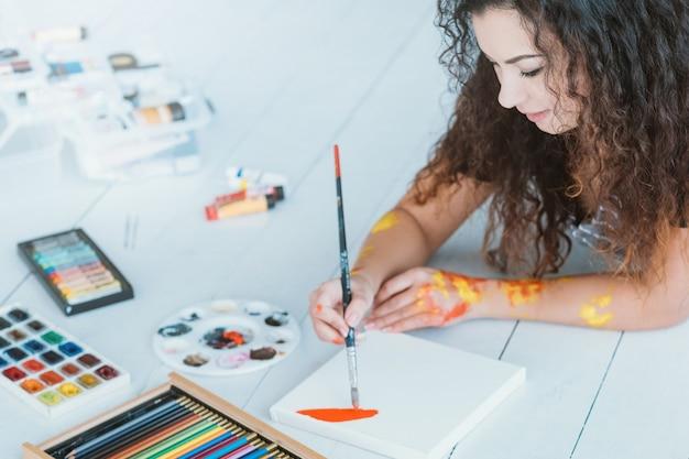 Jolie dame appréciant la peinture à l'aquarelle. crayons de couleur, palette sur parquet blanc.