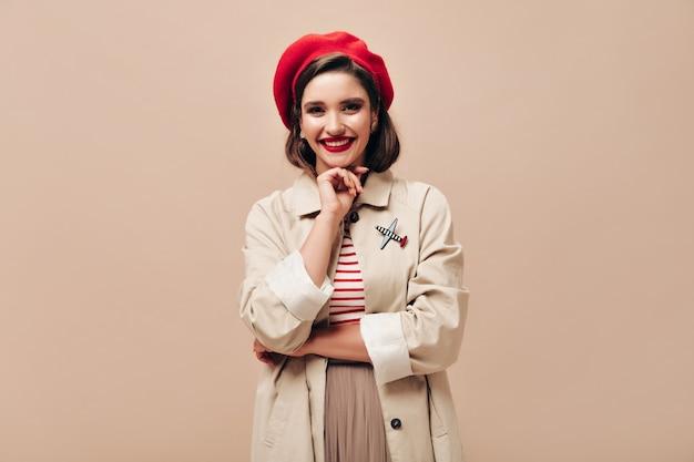 Jolie dame au béret rouge et sourires de tranchée sur fond beige. heureuse jeune femme au chapeau rouge et manteau léger sourit à la caméra.