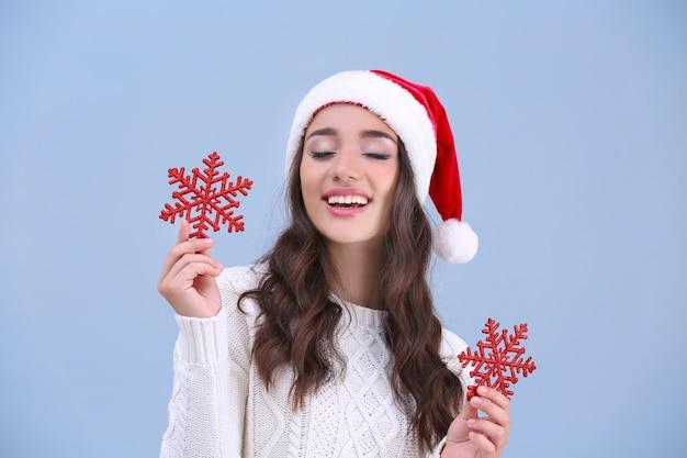 Jolie dame au chapeau de noël tenant des flocons de neige rouges