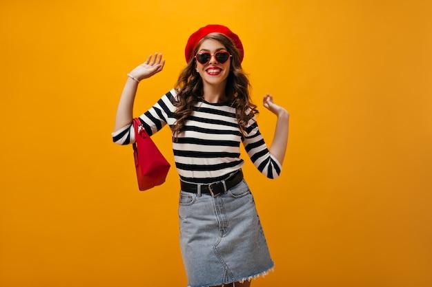 Jolie dame au chapeau rouge et chemise pose sur fond orange. avec sac. belle femme en chemisier rayé et jupe élégante souriant.