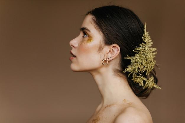 Jolie dame aux cheveux noirs avec une peau pâle regardant vers le haut. photo intérieure d'une fille debonair avec une feuille verte dans les cheveux.