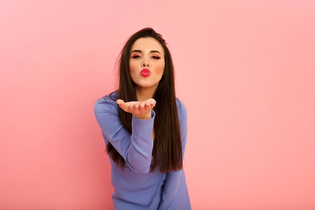 Jolie dame aux grandes lèvres rouges et coiffure longue brune posant sur le fond rose en studio. robe à la mode sur son corps galbé. décolleté et manches longues. jeune femme sexy, bouche ouverte
