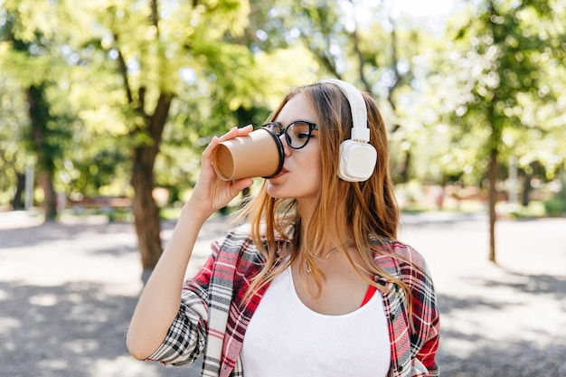 Jolie dame buvant du café avec plaisir dans la rue. charmant modèle féminin dans un casque blanc debout devant les arbres.