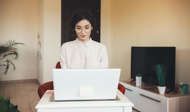 Jolie dame caucasienne avec des lunettes et des vêtements de cérémonie a une réunion en ligne à l'ordinateur portable de la maison